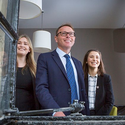 Head master smiling in window with pupils trio nav square.jpg